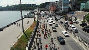 Luchthommelschot van groep fietser in het heldere sportieve slijtage berijden langzaam door stadscentrum langs kade stock footage