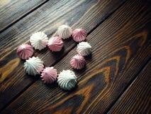 Luchtig roze en wit schuimgebakje op houten achtergrond stock foto's