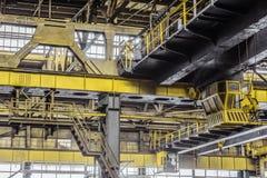 Luchtkranen met een kraanmachinistencabine en haken in een het kaderworkshop van het multi-spanwijdtemetaal stock foto's
