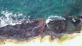Luchtkustlijnmening en golven die op rotsachtige klippenoever verpletteren stock video