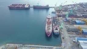 Luchtlandschapsvrachtschip in industriële scheepswerf Overzeese schepen die zich op parkeerterrein in de hommelmening van de werf stock videobeelden