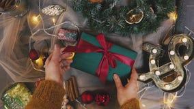 Luchtlengte die van vrouw rood lint op gift binden Lockdown van vrouwelijke verpakking huidig bij houten lijst wordt geschoten di stock videobeelden