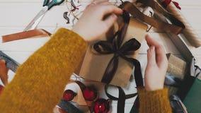 Luchtlengte die van vrouw rood lint op gift binden Lockdown van vrouwelijke verpakking huidig bij houten lijst wordt geschoten di stock footage