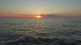 Luchtlengte Oceaanvlieg over bij zonsondergang, net boven de oceaangolven die de zon onder ogen zien stock video