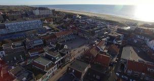 Luchtlengte van de stad dichtbij het overzees Hommel die boven daken van de huizen in Nederland vliegen stock videobeelden