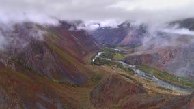 Luchtlengte van een bewolkte bergvallei Hierboven het vliegen stock footage