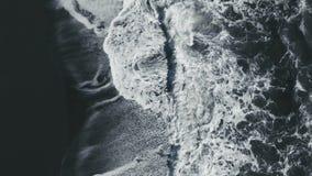 Luchtlengte van golven die tegen zwart zandstrand breken in Vik Iceland stock footage