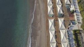 Luchtlengte van kustlijn met paraplu's op zandig strand stock video