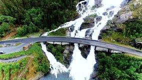 Luchtlengte van Langfossen-waterval in Noorwegen en wegbrug met auto's die boven de waterval overgaan stock videobeelden