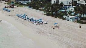 Luchtlengte van mensen op het zandige oceaanstrand dichtbij luxueus hotel en exotische bomen op zonnig eilandenstrand, Miami stock footage
