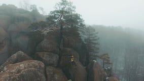 Luchtmening bij de mensenzitting op de bovenkant van de rots in de winterbergen met mist worden behandeld die stock videobeelden