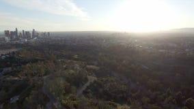 Luchtmening die hoog boven Los Angeles bij zonsondergang toenemen stock footage