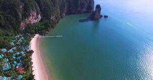 Luchtmening die over het amaizing van hotelhuizen vliegen naar mooie groene bergen en wit zandig strand Het eiland van Krabi stock video