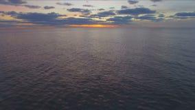 Luchtmening die over water bij zonsondergang vliegen stock videobeelden