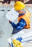 Luchtmening die van arbeider in weerspiegelend vest en bouwvakker de bouwplannen onderzoeken stock afbeelding