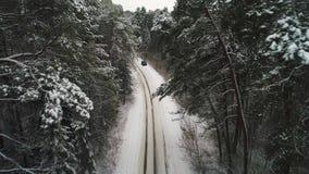 Luchtmening die van auto zich in de winterbos bewegen stock video