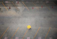Luchtmening die van bedrijfsvrouw gele paraplu houden en alleen door de achtergrond van het autoparkeerterrein lopen Stock Foto's