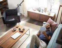 Luchtmening die van de Mens op Sofa At Home Watching Movie op Digitale Tablet liggen royalty-vrije stock foto's