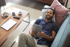 Luchtmening die van de Mens op Sofa At Home Watching Movie op Digitale Tablet liggen royalty-vrije stock afbeeldingen