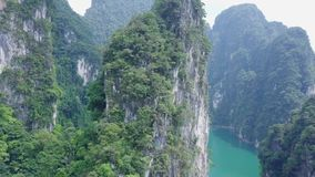 Luchtmening die van kalksteenrotsen van water toenemen Hoogste mening van bergen in Khao Sok National Park op Cheow Lan Lake stock video