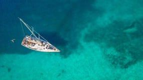 Luchtmening die van varende boot op koraalrif verankeren stock fotografie