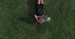 Luchtmening die van vrouw op het gras liggen terwijl de hommel de zonnebril van haar gezicht opstijgt stock footage