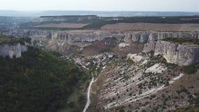 Luchtmening: een spanwijdte in het midden van een canion, aan één kant van de klip, aan de andere kant van het bos in het midden stock footage