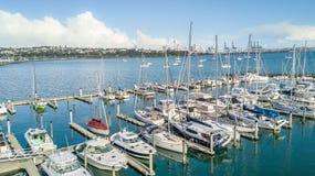 Luchtmening over een jachthaven en rustende boten met de stadscentrum van Auckland op de achtergrond Ergens in Nieuw Zeeland royalty-vrije stock foto's