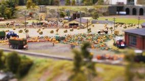 Luchtmening over een stuk speelgoed in de voorsteden met hooi, tractoroogst in de herfsttijd in Rusland Langzame Motie 3840x2160 stock footage