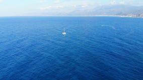 Luchtmening over klein wit jachtzeil in blauwe overzees stock videobeelden