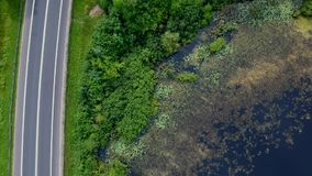 Luchtmening over snel drijfauto's op asfaltweg op bosgebied met meer stock videobeelden
