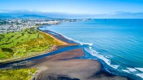 Luchtmening over Taranaki-kustlijn met een kleine rivier en Nieuw Plymouth op de achtergrond Taranakigebied, Nieuw Zeeland stock foto