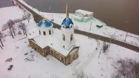 Luchtmening over witte kerk in de winter tijdens zware sneeuw Luchtmening van Kerk in Rusland klem Kleine Stadskerk stock video