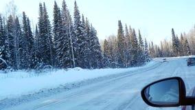Luchtmening van auto het drijven langs de sneeuw mooie bergweg en de zon die door de bomen glanzen Mening over spiegel van stock video