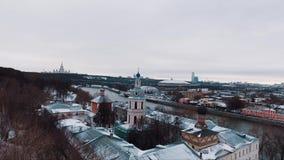 Luchtmening van behandeld in sneeuw orthodox klooster op rivierkust stock video