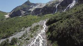 Luchtmening van berglandschap Het satellietbeeld van bergen behandelde bos, bomen met stromende rivier, tegen de hemel stock footage