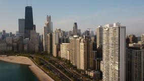 Luchtmening van Chicago, Amerika op beneden Hommel die vanaf van de binnenstad op de kust van het meer van Michigan vliegen stock video