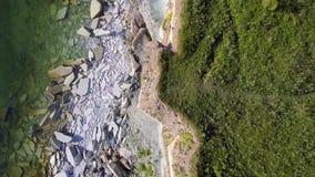 Luchtmening van de kustlijn langs het overzees met een klip met grote stenen en het groene gras stock video