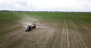 Luchtmening van de landbouw van tractor die en op gebied ploegen bespuiten stock video