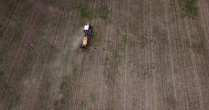 Luchtmening van de landbouw van tractor die en op gebied ploegen bespuiten stock videobeelden