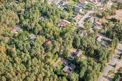 Luchtmening van de rand van een dorp met kleine familiehuizen, de waarvan eigenschappen in het dichte bos doordringen royalty-vrije stock foto's