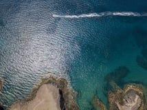 Luchtmening van de scherpe kusten en de stranden van Lanzarote, Spanje, Kanarie De rode rubberboot navigeert gevolgd door watercr stock foto's