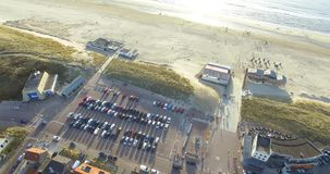 Luchtmening van de stad en de kust Hommelcamera die van huizen aan strand en Noordzee opheffen stock video