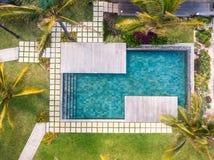 Luchtmening van de toevlucht van het luxehotel met zwembad met trede en houten die dek door palmen wordt omringd royalty-vrije stock afbeeldingen