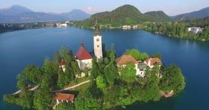 Luchtmening van de Veronderstelling van de kerk van Maria op Afgetapt meer , Slovenië stock footage