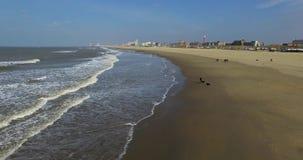 Luchtmening van de winterkust met mensen en overzeese golven Hommel die langs strandkust vliegen stock videobeelden