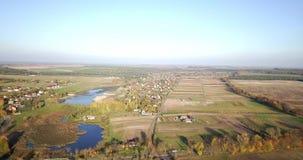 Luchtmening van de zomerplatteland met landbouwgebieden en huizen Landbouwgrondgebied in platteland met huizen en stock videobeelden