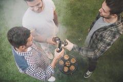 Luchtmening van drie jonge mensen die barbecue en het clinking maken royalty-vrije stock afbeeldingen