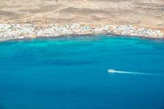 Luchtmening van een boot in de oceaan met de kustlijn van het eiland van La Graciose in Lanzarote, Canarische Eilanden Spanje Stock Foto's