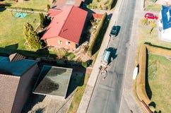 Luchtmening van een eenvoudig losgemaakt huis op een geasfalteerde grijze dorpsweg, waarop een stratemaker het onderhoudswerk uit royalty-vrije stock foto